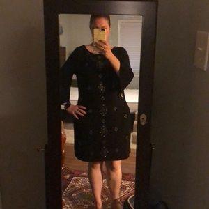 Black dress with metallic embellishments.